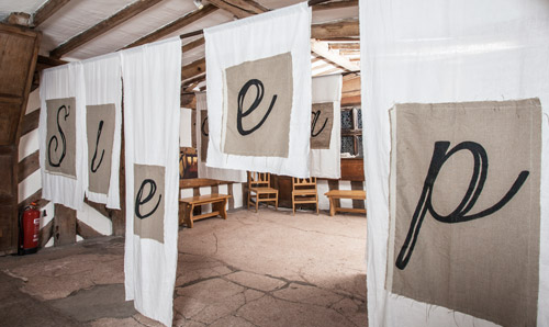 The word 'sleep' stitched onto hanging sheets